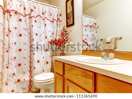 Simple bedroom with flowery curtain shower and wood sink cabinet.