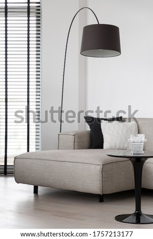 Simple beige sofa and black coffee table under stylish lamp in living room with big window