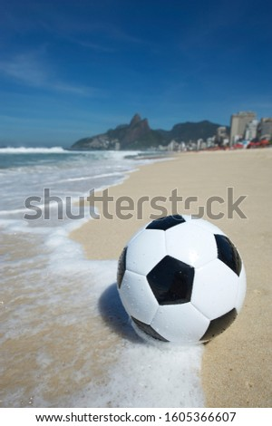 Simple black and white soccer ball (known as a futebol, or football) in the waves on the shore of Ipanema Beach in Rio de Janeiro, Brazil Foto stock ©