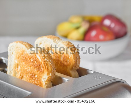 Simple breakfast scene of toast in a toaster with a bowl of fruit behind