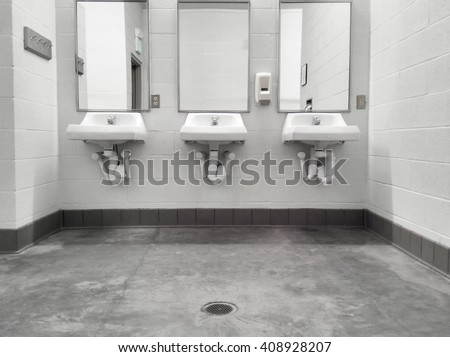Simple but clean public washroom, row of sinks and mirrors, grungy faded-color mobile shot