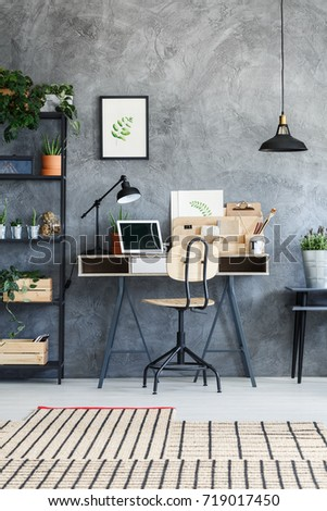Simple chair at desk with black lamp, cactus, laptop and cup of coffee in dark home office