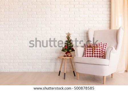 Simple Christmas living room with armchair and small Christmas tree