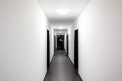 Simple clean newly built generic modern new real estate block of flats interior, long white corridor with black doors, perspective. New bought apartment, new home, hallway abstract concept, copy space