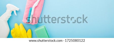 Simple cleaning set for different surfaces in kitchen, bathroom and other rooms. Spring regular cleanup. Light pastel blue background. Closeup. Top view.  Wide banner. Empty place for text or logo. Stock photo ©