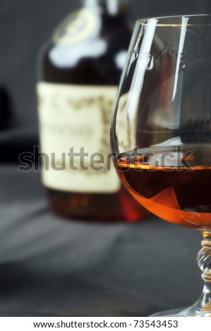 Simple composition of glass and bottle cognac. black background