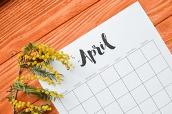 Simple desk calendar for April 2021 with spring flowers. Place for text. Deadline concept with sheet of monthly calendar.