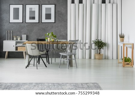 Simple dining room with potted plants, monochromatic posters, white tubes and cupboard #755299348