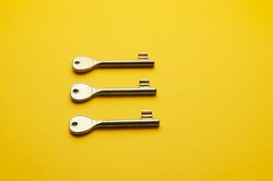 Simple door keys organized in a row over bright yellow background