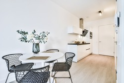 Simple elegant minimalist interior design of modern apartment with open space kitchen and round dining table with wicker chairs