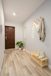 Simple entryway with wooden floor panels and shoe bench