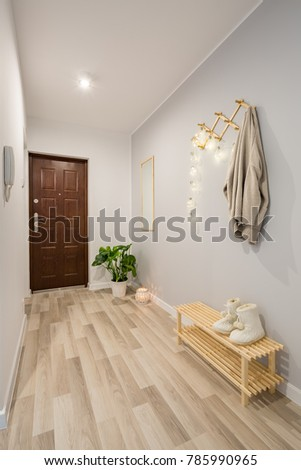 Simple entryway with wooden floor panels and shoe bench #785990965