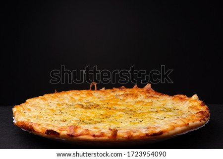 Simple four cheese delivered pizza with crunchy crest and golden yellow orange tint studio low key still life against a dark background