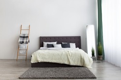 Simple furniture for modern contemporary apartment design. Bed with blanket and pillows, mirror, stairs as decorative element on gray wall background in modern bedroom interior, copy space, mockup