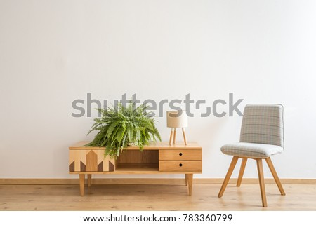 Simple, gray chair stranding next to a wooden cupboard with small lamp and fern on it #783360799