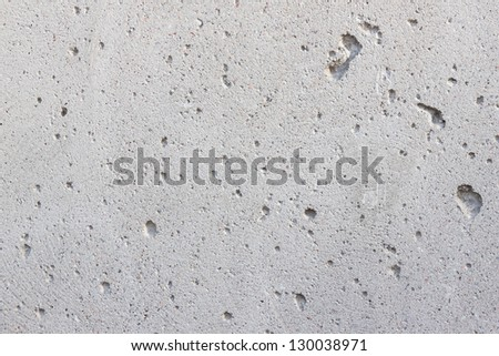 Simple gray concrete wall background with small holes