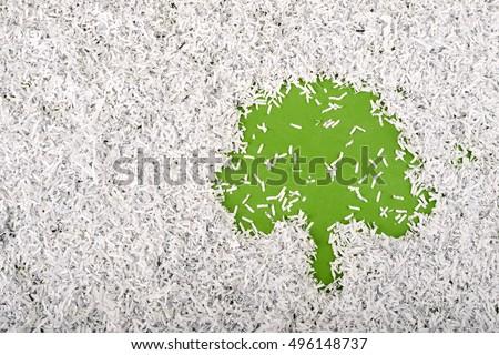 simple green tree symbol made inside big heap of shredded paper