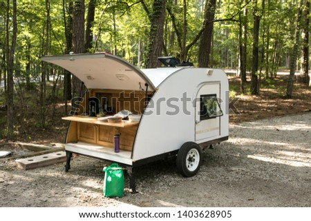 Simple home built teardrop trailer set up at campsite in the forest. #1403628905