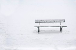 Simple image of a park bench in the snow.