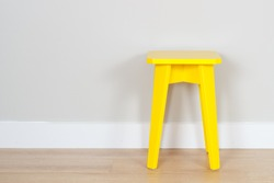 simple interior with a yellow stool and copy space on the wall