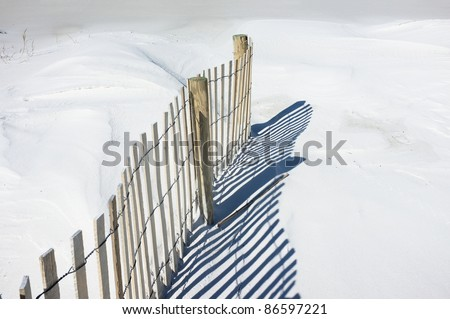 Simple landscape of sand fence and shadows on snowy white dunes at the beach. Sand fences play a vital part in conserving and growing sand dunes. Tiny bird tracks are evident to the left of the fence. - stock photo