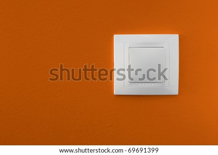 Simple light switch on a orange wall - stock photo