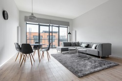 Simple living room with dining area, wooden floor, gray walls and big balcony windows
