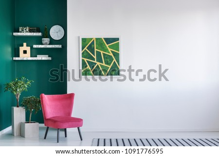 Simple living room with red armchair, abstract painting and clock on the wall, plants in pots, carpet on the floor and bookshelves #1091776595