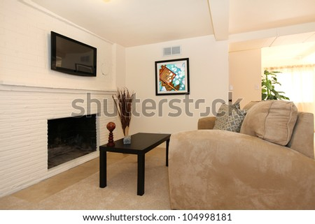 Simple living room with TV and fireplace with beige sofa. - stock photo
