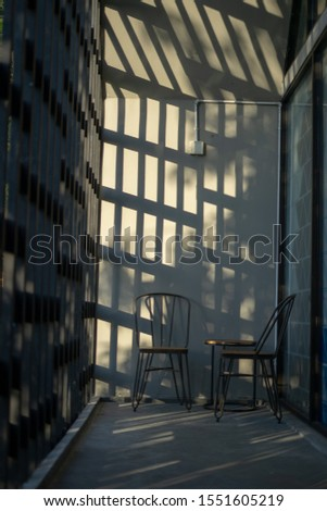 Simple lounge with square shadow and sun light with two chair and one small table spot on the corner. Modern design of lounge and electricity. Taken from low angle and middle angle