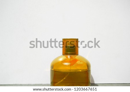 Simple, minimal, monochromatic photograph of a bright, delicate and fancy yellow bottle container over a white background  #1203667651