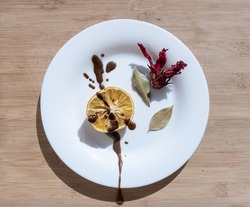 Simple minimalistic symmetric inedible composition with white plate in the middle and lemon, chocolate and hibiscus flower in it