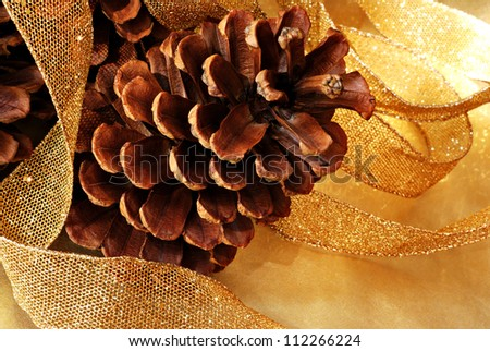 Simple natural holiday decor with pine cones and sparkly gold mesh ribbon on gold metallic paper.  Macro with shallow dof.