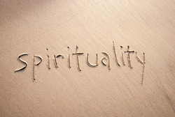 Simple non-demonitational spirituality message handwritten in lowercase letters on textured sand beach