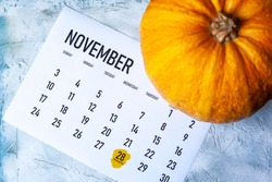 Simple 2019 November monthly calendar on table with a pumpkin. Thanksgiving day marked.