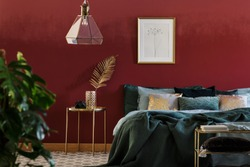 Simple poster hanging above bed with many cushions and green blanket standing in bedroom interior with golden furniture