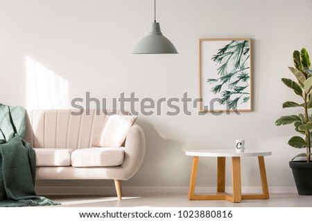 Simple poster hanging on the wall in bright living room interior with sofa and wooden table with tea mug