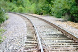 Simple Railroad Tracks Leading from Right to Left. Tracks with a foreground focus leading the eye down to a vanishing perspective to the bottom left.