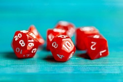 Simple red RPG board game dice set. Multiple role playing game polyhedral dice laying on the table, blue background. Tabletop games accessories, chances and randomness, luck abstract concept