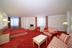 Simple room with double bed with red linen, red carpet and armchairs.