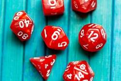 Simple RPG polyhedral board game dice set. Lots of red dice on blue wooden background closeup, shot from above, top view. Fun role playing games roll, chances, randomness and gambling abstract concept