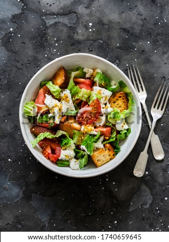 Simple rustic italian salad with fresh tomatoes, ciabatta bread, mozzarella cheese, green salad with olive oil on a dark background, top view