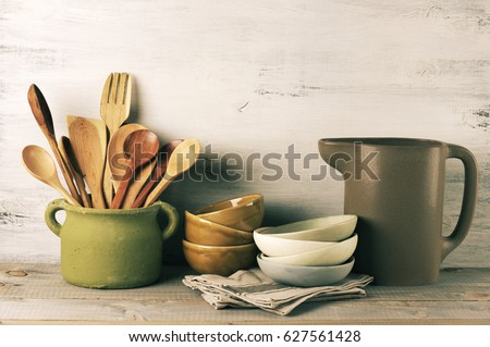 Simple rustic kitchenware against wooden wall: rough ceramic pot with wooden cooking utensil set, stacks of ceramic bowls and jug. Filtered image.