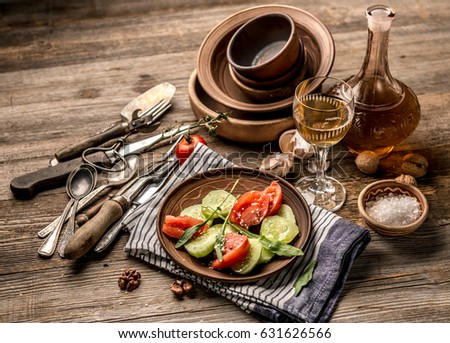 Simple salad of cucumers and tomatoes, rustic dishes and nice cotton napkin on the table