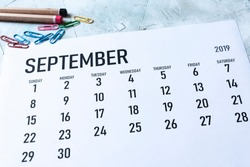 Simple 2019 September monthly calendar on table with office supplies