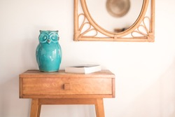 Simple side table timber with green ceramic owl figure and cane mirror on the wall