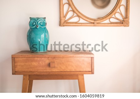 Simple side table timber with green ceramic owl figure and cane mirror on the wall  Сток-фото ©