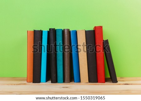 Simple Simple composition of many hardback books, unprocessed books on a wooden table and a green background. back to school. Copy space. Education. #1550319065