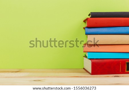 Simple Simple composition of many hardback books, unprocessed books on a wooden table and a green background. back to school. Copy space. Education. #1556036273