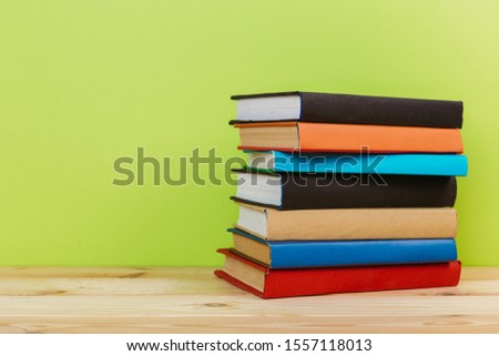 Simple Simple composition of many hardback books, unprocessed books on a wooden table and a green background. back to school. Copy space. Education. #1557118013